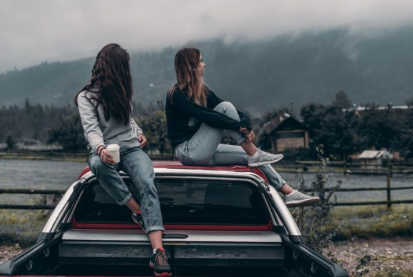 Two millennial girls sitting on top of vintage car