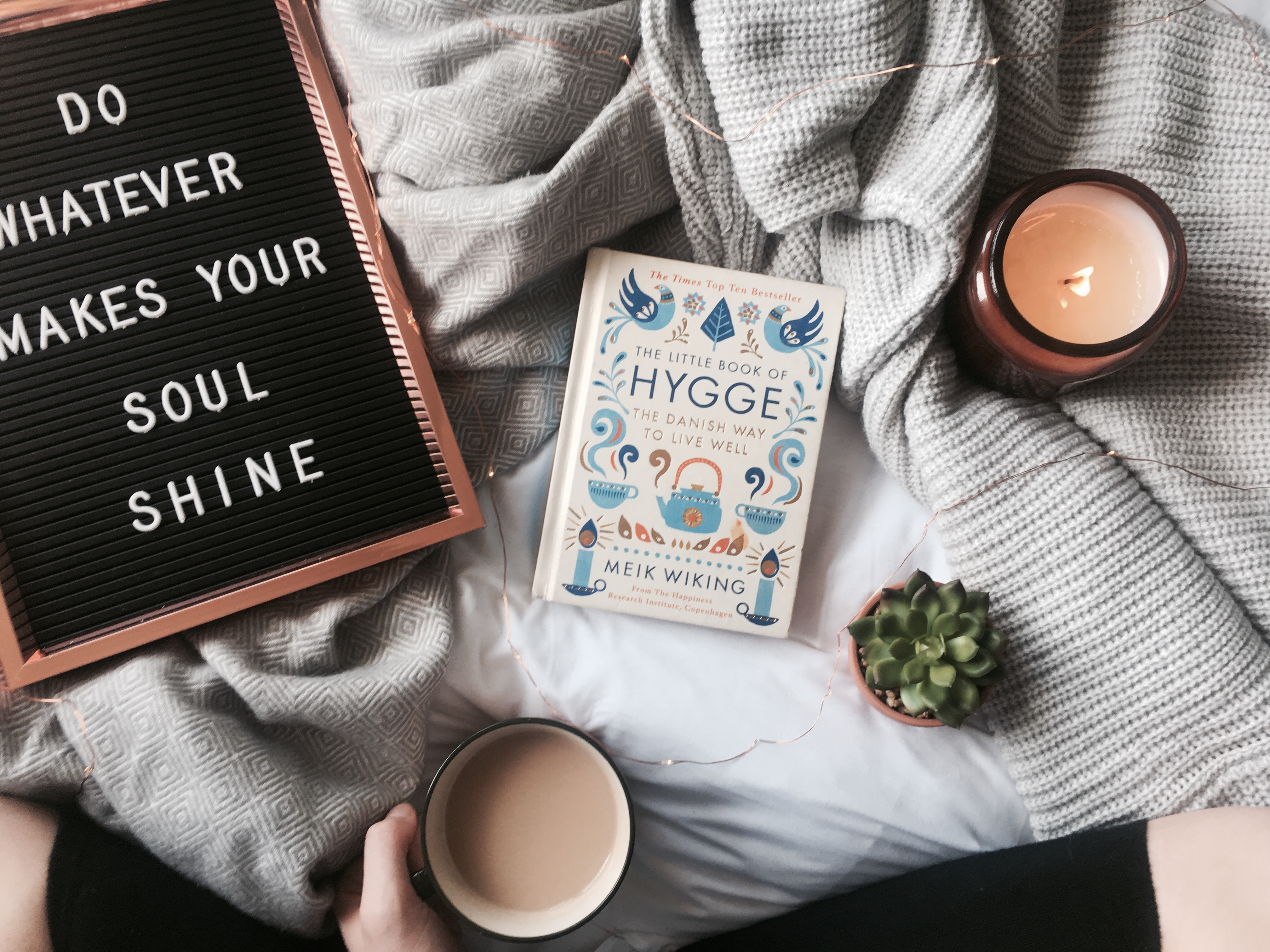 coffee and books in the middle of a bed