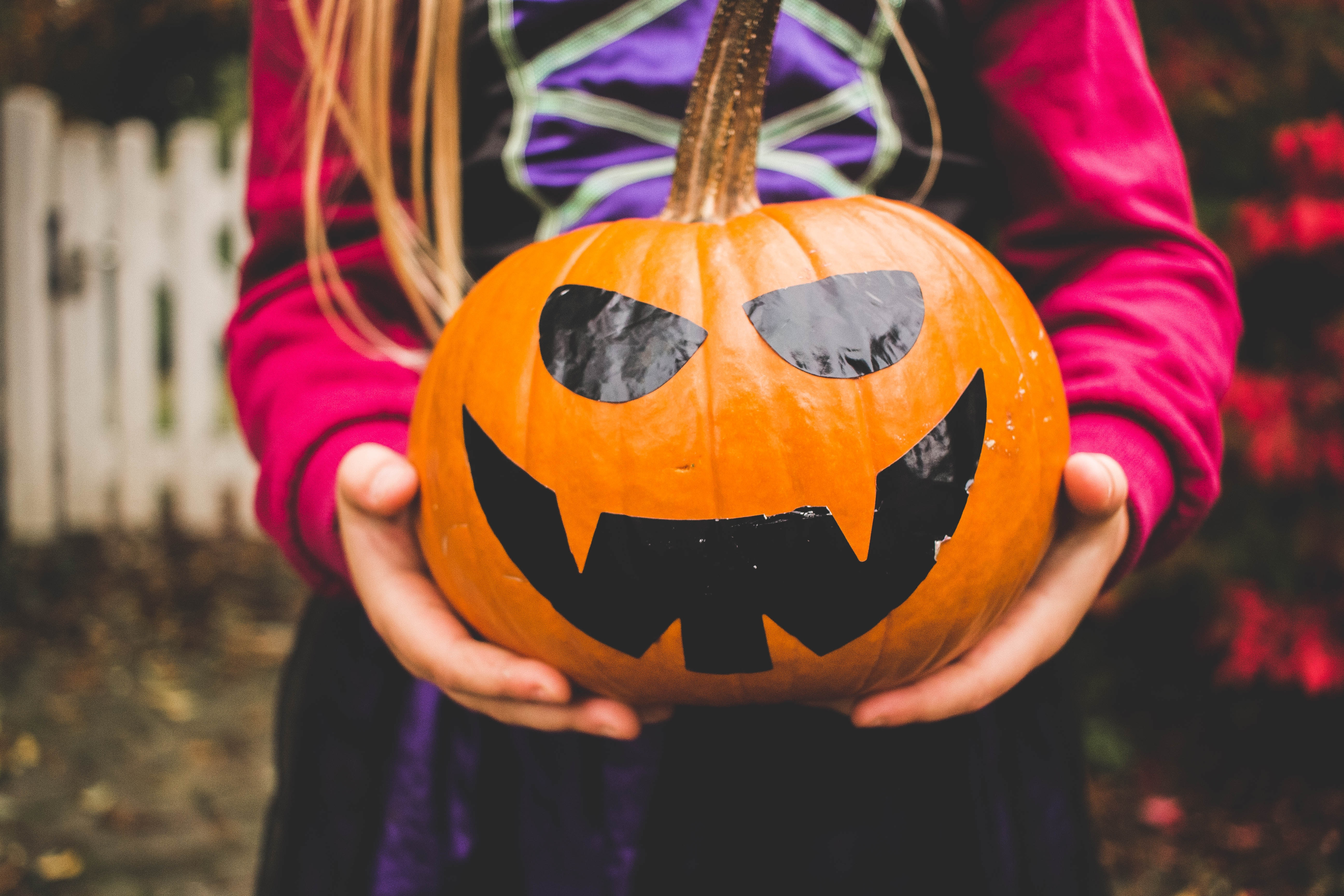little girl in costume holding a pumpkin with carvings