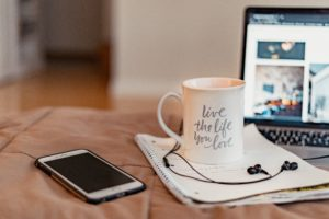 coffee mug with laptop and phone in background