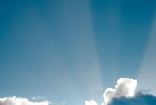 the sky with clouds and light shining through