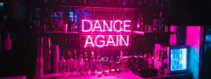 neon dance again sign on wall with liquor bottles around