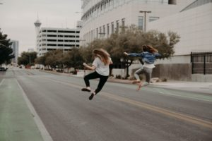 two women jumping on a empty city street